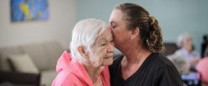 daughter embraces elderly mother