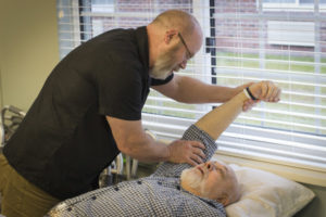 a physical therapist helps a man with his shoulder